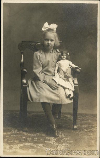 Little Girl with White Bow in Hair Holding Doll While