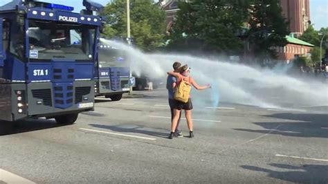 Kissing G20 protesters blasted by water cannon during